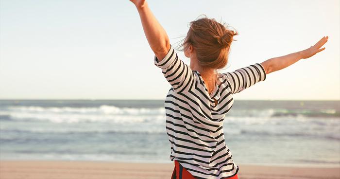 mulher com os braços abertos na praia